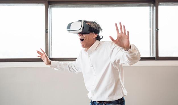 Surpreso homem sênior usando um fone de ouvido de realidade virtual no quarto
