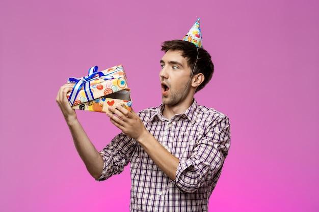 Surpreso jovem bonito, abrindo o presente de aniversário sobre parede roxa.