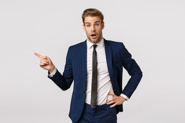 Surpreso, jovem empresário sem palavras, com cabelos loiros, cerdas, vestindo terno clássico, iniciando carreira em nova empresa, fazendo perguntas sobre colegas de trabalho, apontando para a esquerda e parecendo divertido