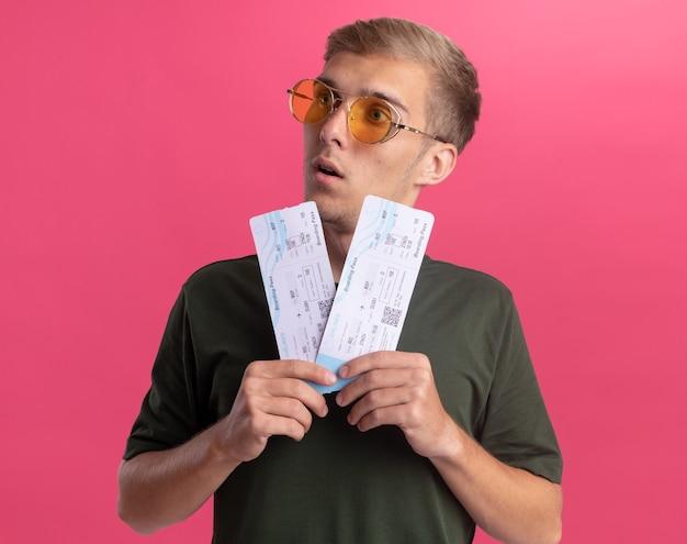 Surpreso, olhando para o lado, jovem bonito vestindo camisa verde e óculos, segurando ingressos isolados na parede rosa