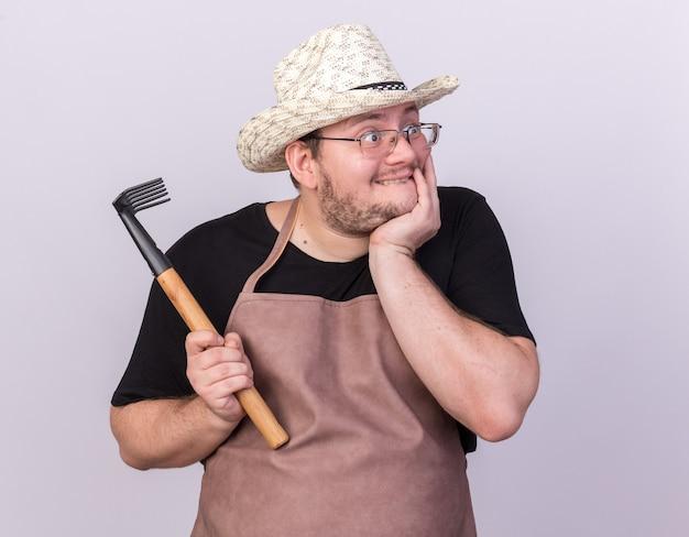 Surpreso, olhando para o lado, jovem jardineiro usando chapéu de jardinagem, segurando o ancinho e colocando a mão embaixo do queixo, isolado na parede branca