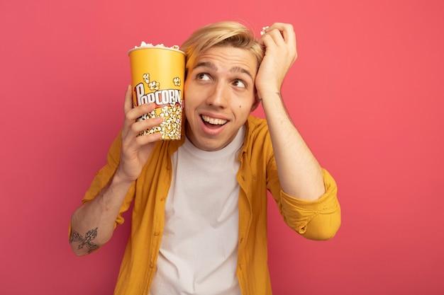 Surpreso, olhando para o lado, jovem loiro de camiseta amarela segurando um balde de pipoca em volta do rosto isolado em rosa