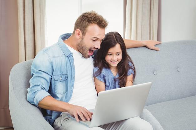 Surpreso pai e filha usando um laptop