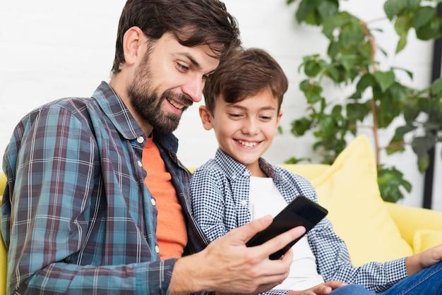 Surpreso pai e filho olhando no telefone