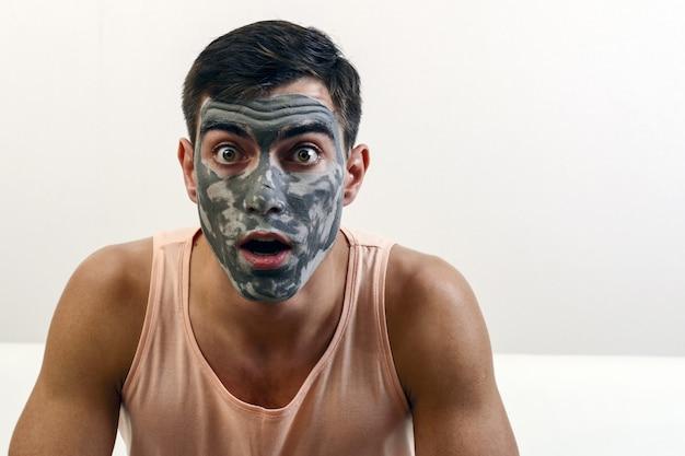 Surpreso retrato de um homem com uma máscara de argila no rosto. cuidados com a pele. copyspace