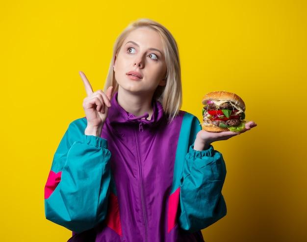 Surprsied garota no estilo de roupas dos anos 80 com hambúrguer no espaço amarelo
