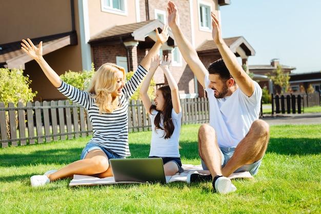 Surto de alegria. família adorável e feliz sentada no gramado em seu quintal e levantando as mãos, aplaudindo alegremente