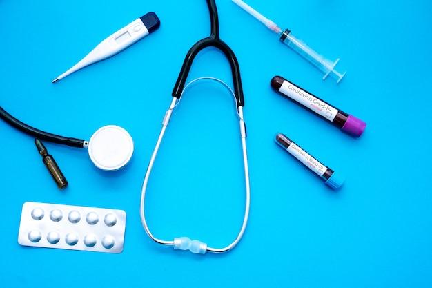 Surto de coronavírus covid-19. conceito de medicina e epidemia. tubo com resultado positivo no exame de sangue, máscara protetora, pílulas medicamentosas, estetoscópio, frasco e seringa, vacina em laboratório