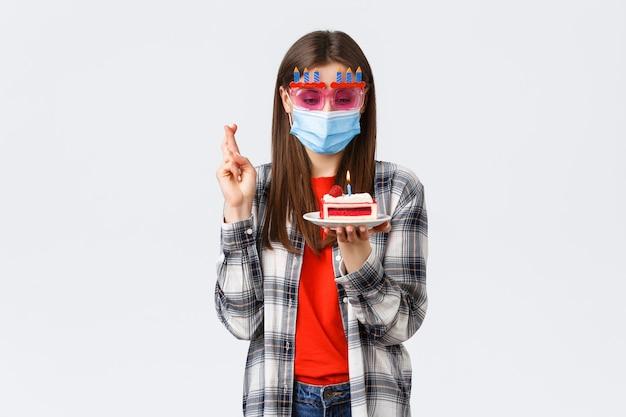 Surto de coronavírus, distanciamento social do estilo de vida e conceito de celebração. garota feliz entusiasmada de óculos e máscara médica comemorar aniversário na quarentena, cruzar os dedos, fazer o desejo no bolo.