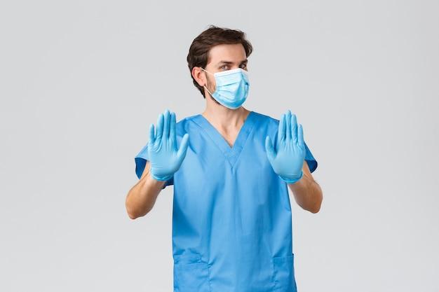 Surto de coronavírus, profissionais de saúde que lutam contra doenças, conceito de hospitais. médico relutante e descontente em máscara médica, luvas e uniforme, show stop, recusar ou rejeitar oferta, acenando com as mãos