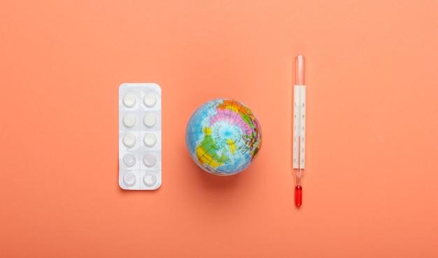 Surto de pandemia ou conceito de aquecimento global. globo, termômetro e bolha de comprimidos em fundo laranja. vista do topo