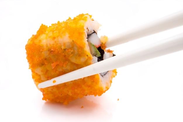 Sushi, alimento japonês, rolo de califórnia com os chopsticks no fundo branco.