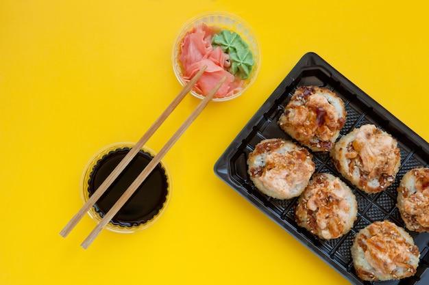 Sushi assado em uma embalagem de plástico em fundo amarelo - plano plano com gengibre e wasabi - conjunto brilhante e delicioso de rolos de sushi em uma caixa de plástico