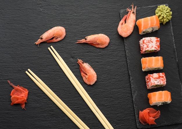 Sushi californiano com caviar tobiko vermelho e fatias de sushi da filadélfia em quadro de ardósia preta, vista superior