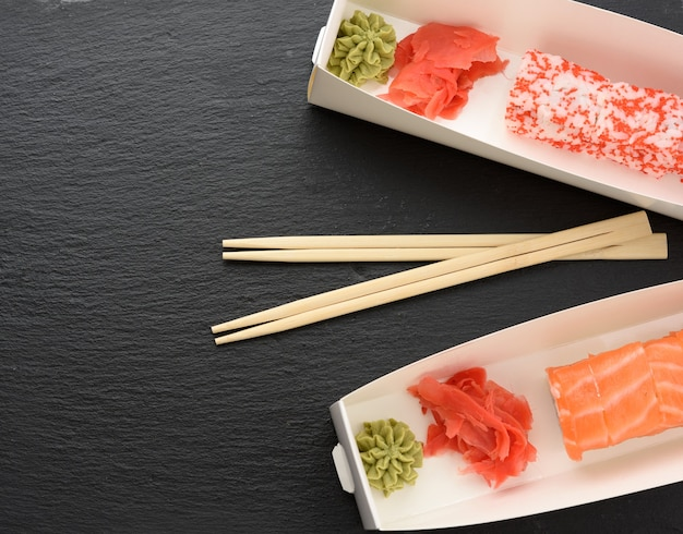 Sushi californiano com caviar tobiko vermelho e fatias de sushi filadélfia com enguia em caixa branca, delivery, vista de cima