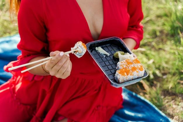 Sushi closeup definir entrega de comida. garota sexy segura sushi com os pauzinhos nas mãos.