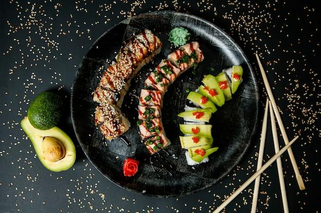 Sushi com abacate, salmão, caranguejo, sementes de gergelim, gengibre e wasabi