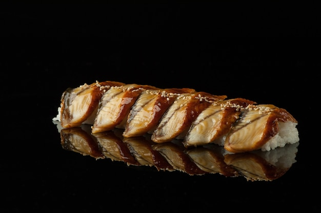 Sushi com arroz e sementes de gergelim em um fundo escuro com reflexo