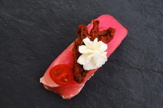 Sushi com atum, tomate seco e cream cheese em chapa de ardósia