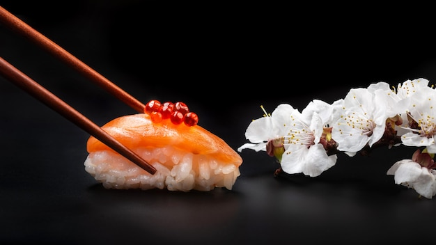 Sushi com caviar vermelho e flores brancas em uma mesa preta. macro close-up.
