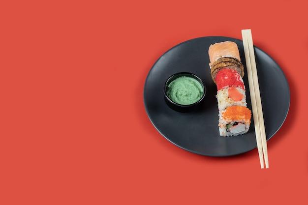Sushi com molhos em uma travessa preta na mesa vermelha.