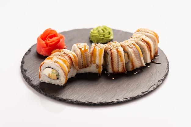 Sushi com peixe enguia em uma pedra redonda preta.