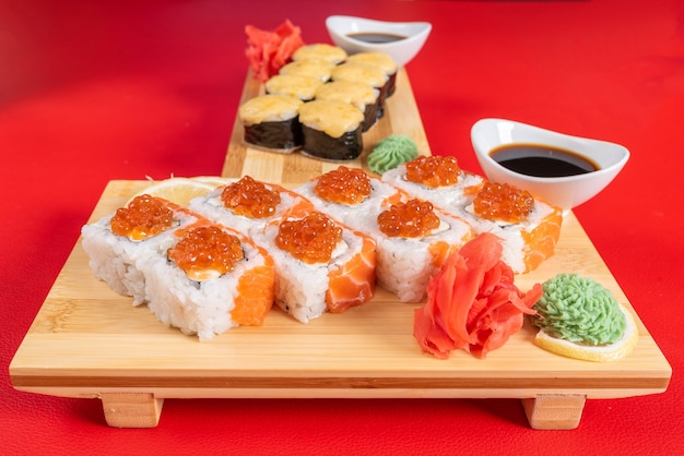 Sushi, com requeijão, salmão e caviar. na prancha. sobre um fundo vermelho. para qualquer propósito.
