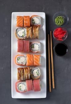 Sushi com salmão, atum e enguia defumada com queijo da filadélfia na chapa branca sobre fundo cinza. servido com molho de soja, wasabi, gengibre em conserva e palitos para sushi. vista de cima