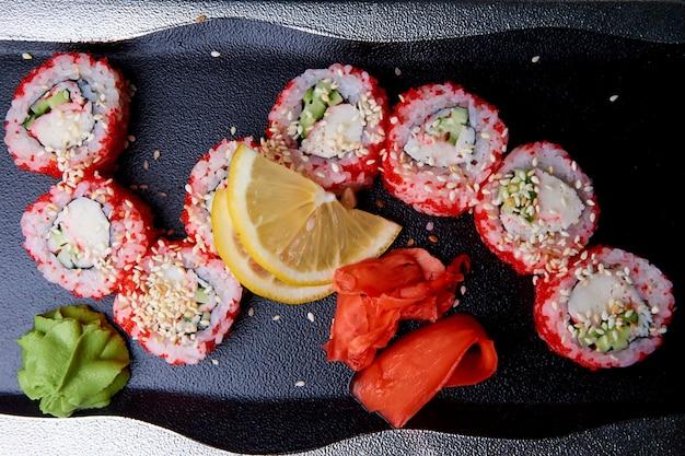 Sushi com wasabi e gengibre na placa.