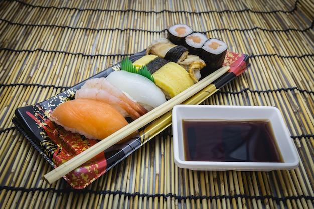 Sushi conjunto sashimi e rolos servidos no prato tradicional e esteira com shoyu japonês