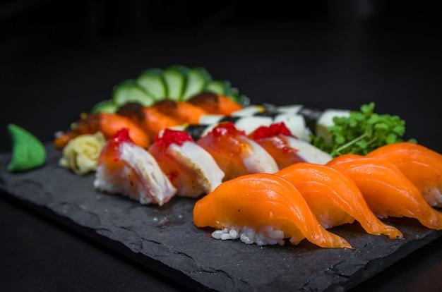 Sushi, cozinha tradicional japonesa. vários deliciosos sushis no prato decorado,