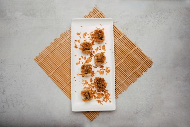 Sushi de arroz com cebola seca em cima do prato branco na esteira de bambu em fundo cinza