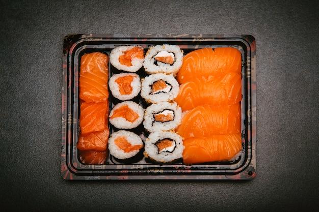 Sushi de arroz sortido dentro da bandeja reutilizável de três tupper preto sobre fundo cinza