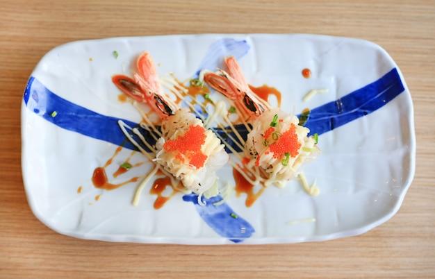 Sushi de camarão com ovo no prato na mesa de madeira. comida japonesa tradicional.