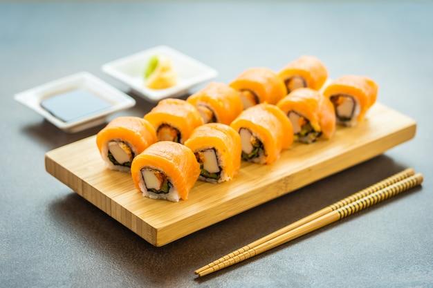 Sushi de carne de peixe salmão roll maki na placa de madeira