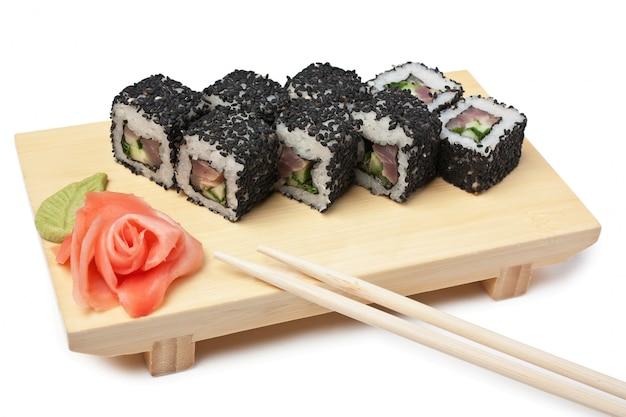 Sushi de comida asiática tradicional na placa de madeira, isolada no espaço em branco