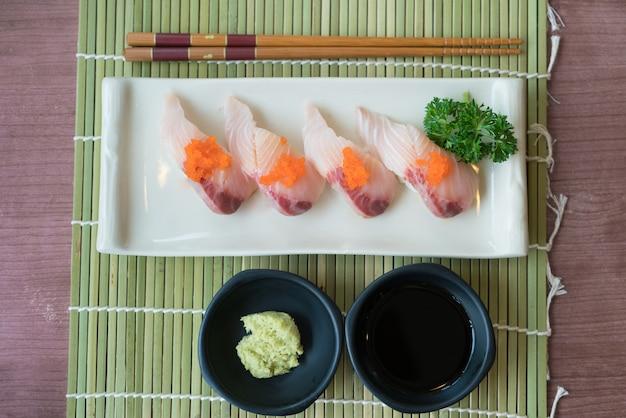 Sushi de hamachi na placa branca junto com o molho japonês e a decoração verde da folha.