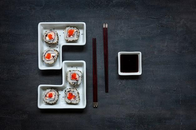 Sushi de mousse de carne de caranguejo japonês com caviar vermelho e pauzinhos