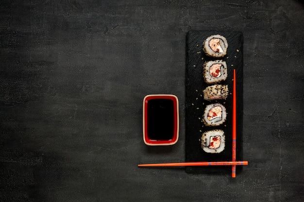 Sushi de mousse de carne de caranguejo japonês com molho de soja na placa de pedra com pauzinhos
