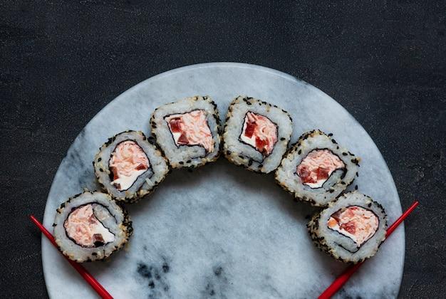 Sushi de mousse de carne de caranguejo japonês na placa de pedra de mármore com pauzinhos
