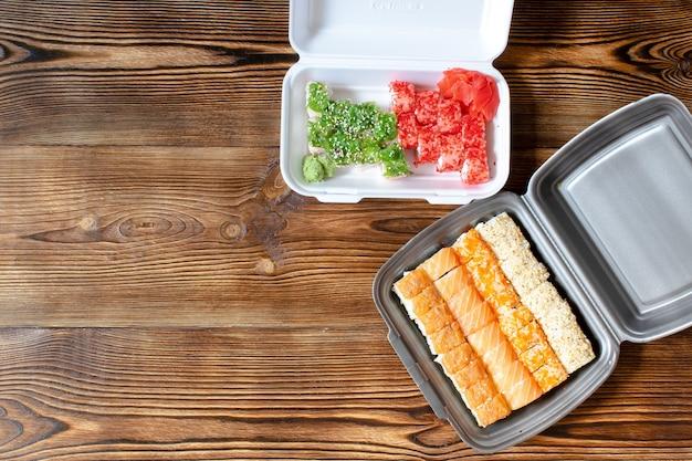 Sushi de peixe rola salmão, gergelim, gengibre e wasabi embalados em um recipiente de plástico descartável para alimentos. frutos do mar