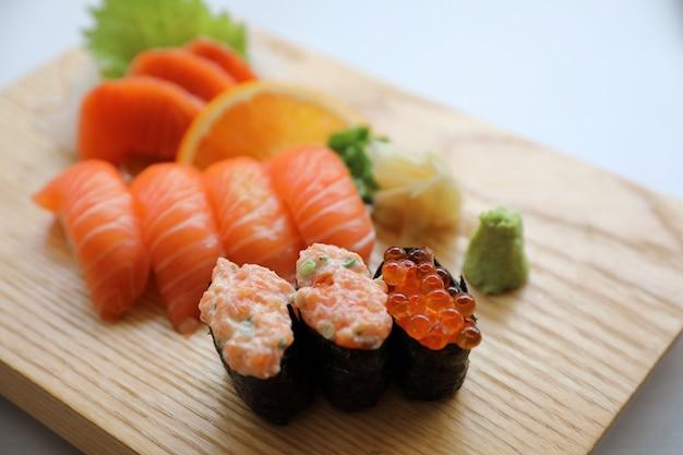 Sushi de salmão e sashimi na placa de madeira comida japonesa