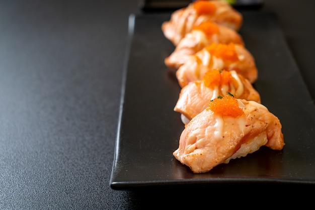 Sushi de salmão grelhado em prato preto - comida japonesa