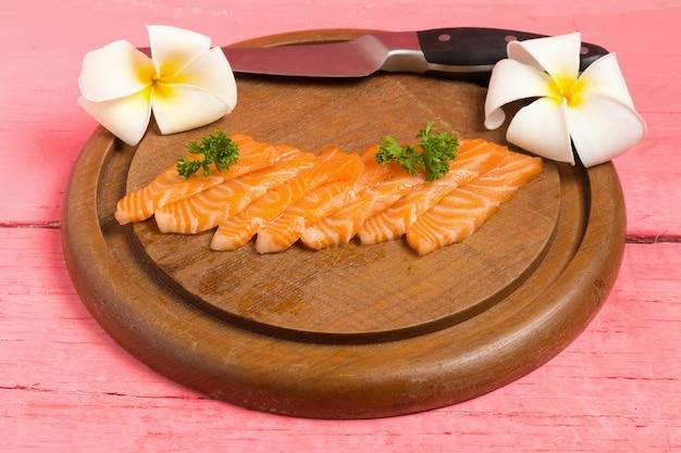 Sushi de salmão na tábua com flor na cor rosa de madeira