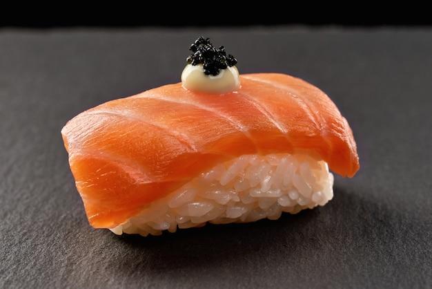 Sushi de saquê nigiri coberto com molho e caviar preto.