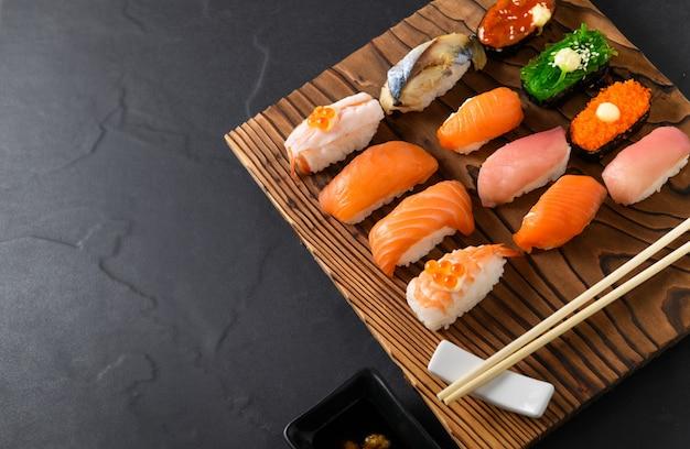 Sushi de sashimi com pauzinhos na placa de madeira