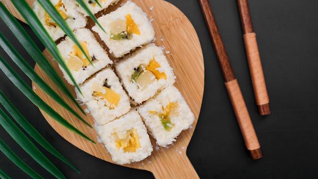 Sushi de sobremesa. kiwi doce, rolos de sushi de abacaxi. sushi em bandeja de madeira