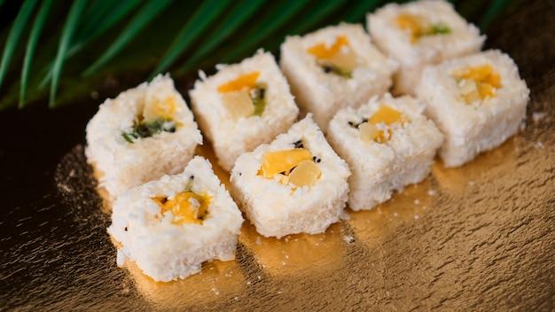 Sushi de sobremesa - rolo com várias frutas e cream cheese dentro. sobre fundo dourado e folha tropical