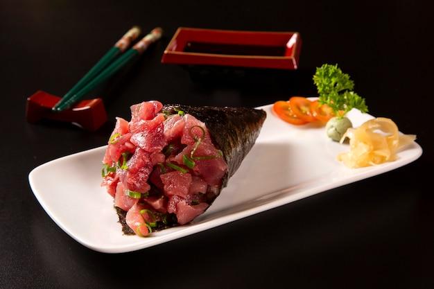 Sushi de temaki de atum em um prato branco em fundo preto