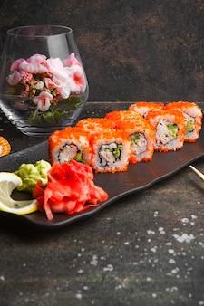 Sushi de vista lateral com gengibre em conserva e wasabi no prato escuro